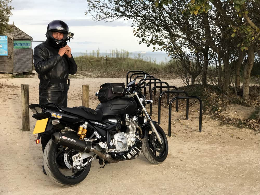 rider in black leathers and helmet with go pro video camera