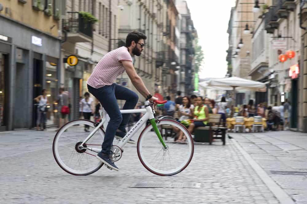 man riding white electric bike in city