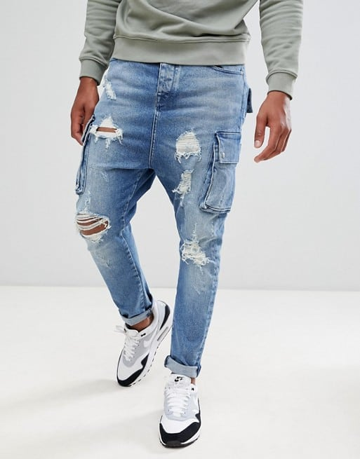 drop crotch jeans in mid wash blue with cargo pockets and rips