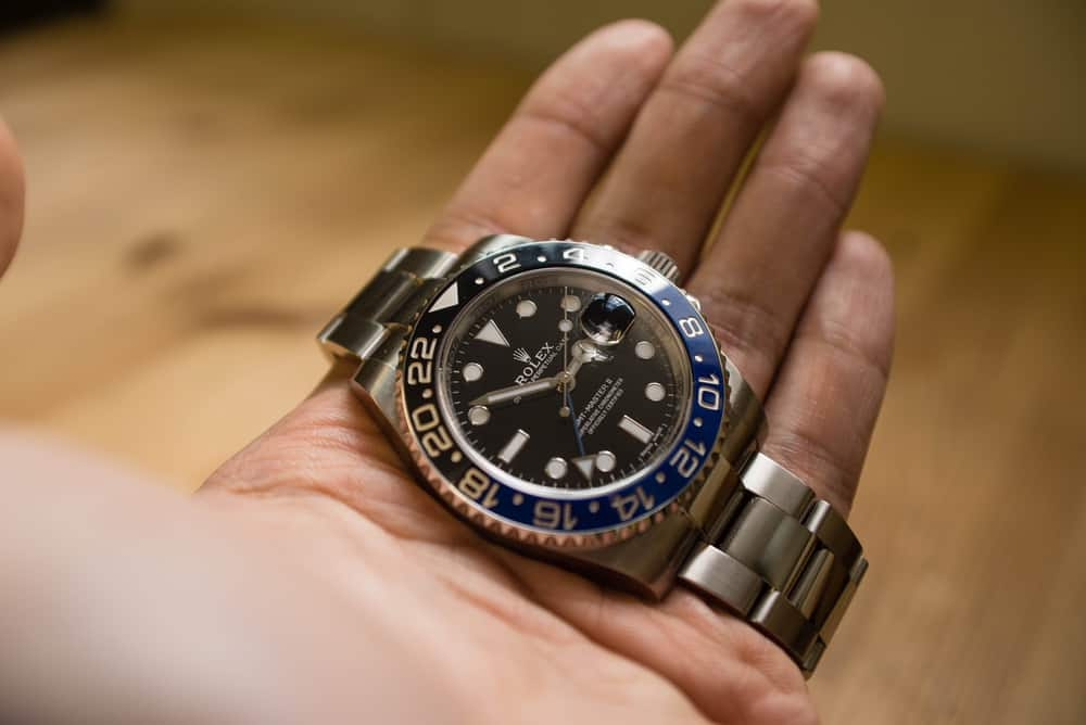 rolex gmt master II on a hand in front of a wood grain background
