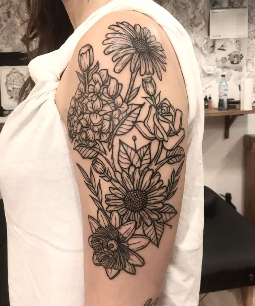Upper arm and shoulder tattoo large black line work rose orchid passion flower and daisy
