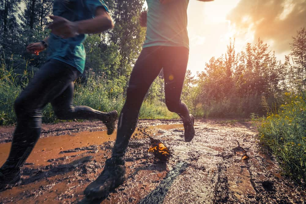 running athletes crossing dirty trail
