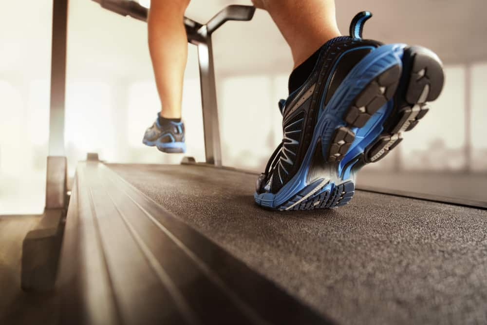 man running on treadmill with black shoes