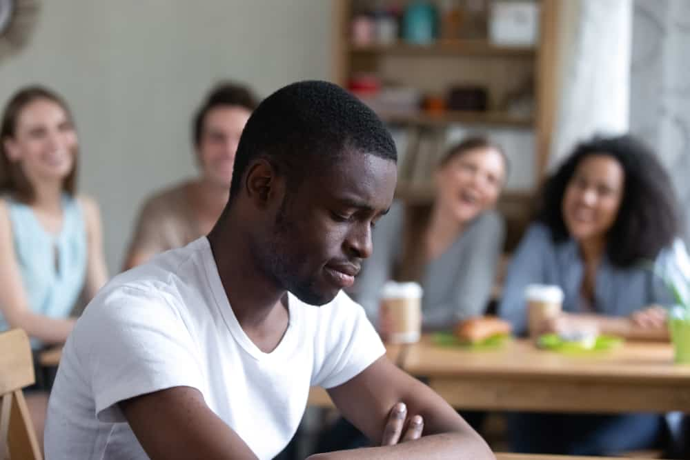 sad african man sitting in cafe