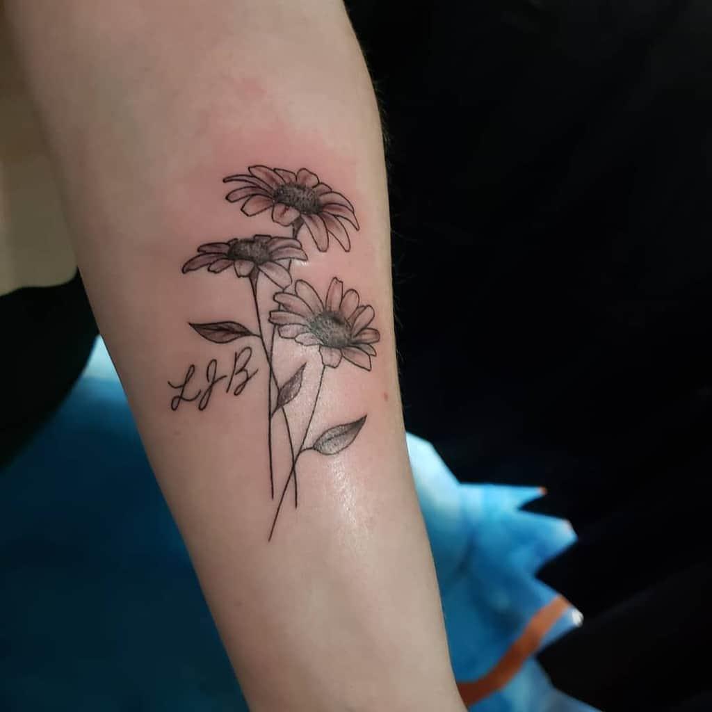 Forearm tattoo black and grey fine line script daisy bouquet
