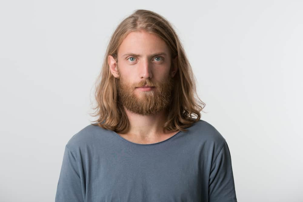 closeup of serious attractive man with beard and blonde long hairs