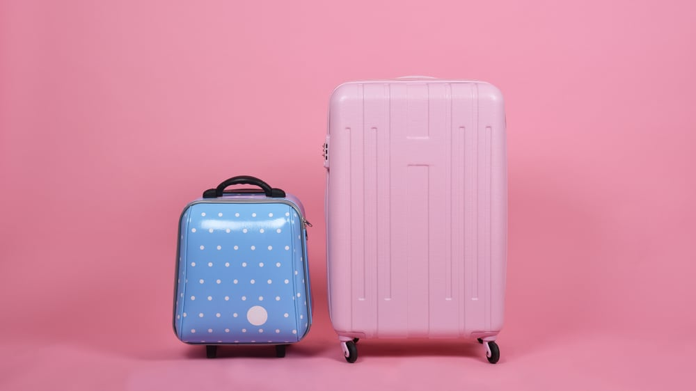 large and small set of luggage suitcase isolated on pink background