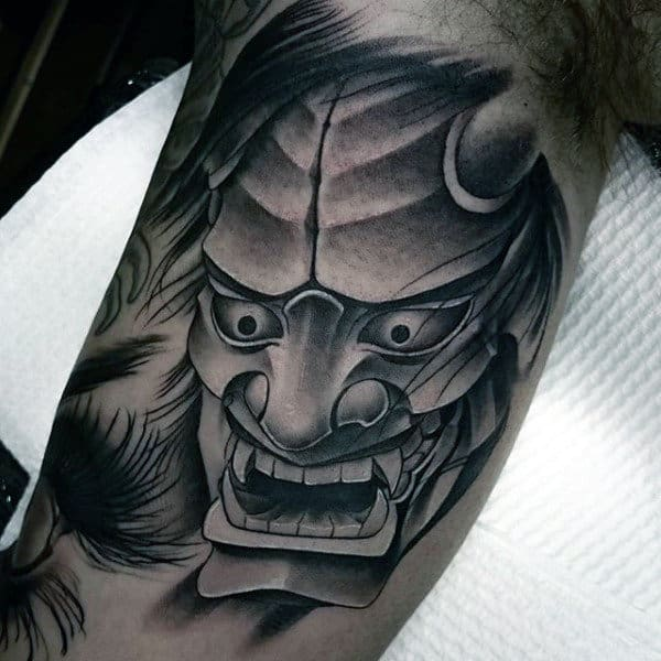 Shaded Black And Grey Hannya Mask Bicep Tattoo On Man