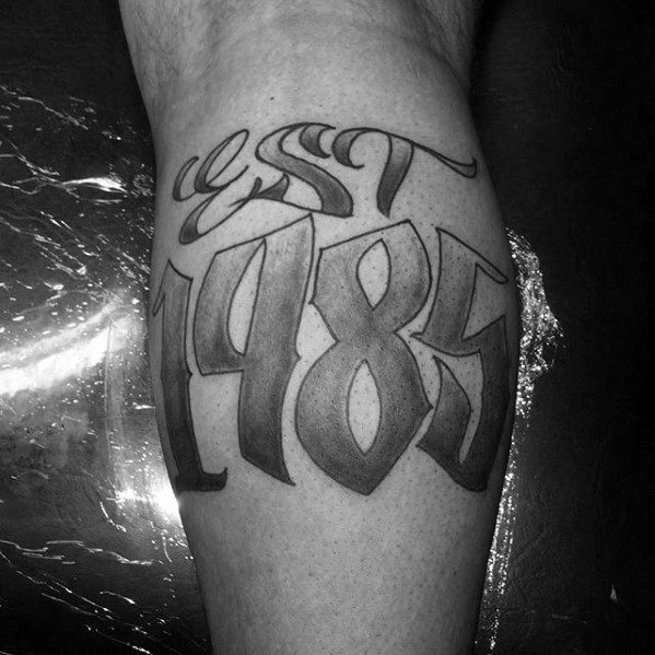Shaded Black And Grey Ink Male Est 1985 Tattoo Design On Leg Calf