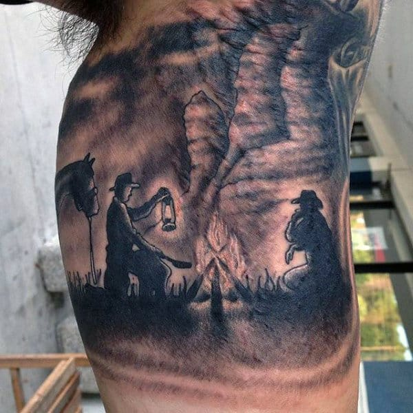 Shaded Blackwork Tattoo Of Western Men By Fire With Horse On Guy