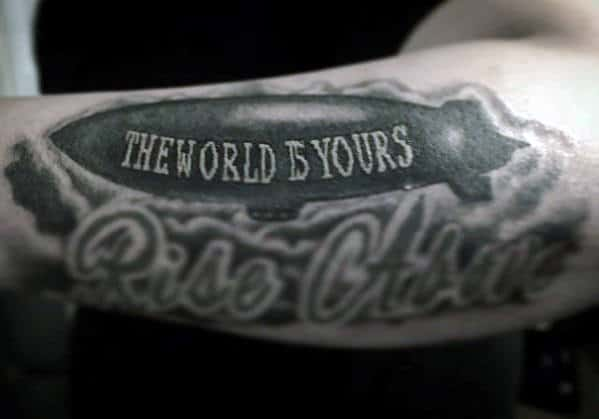 Shaded The World Is Yours Negative Space Blimp Tattoo On Outer Forearm For Men