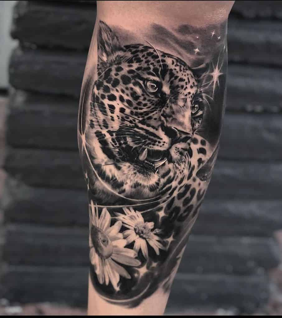 Calf tattoo realistic black and grey shading jaguar with daisies