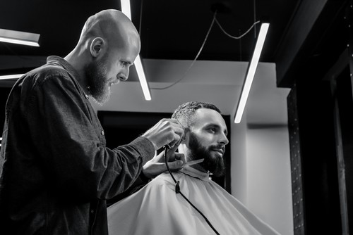 ALD BARBER IS TRIMMING THE HAIRCUT OF HIS BEARDED SERIOUS CLIENT. HE IS USING A HAIR CLIPPER
