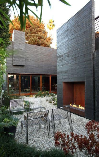 Side Of House Modern Outdoor Fireplace With Pebble Walkway