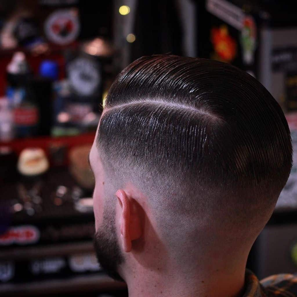 A burst fade haircut with side parted hair and barely noticeable fade transition