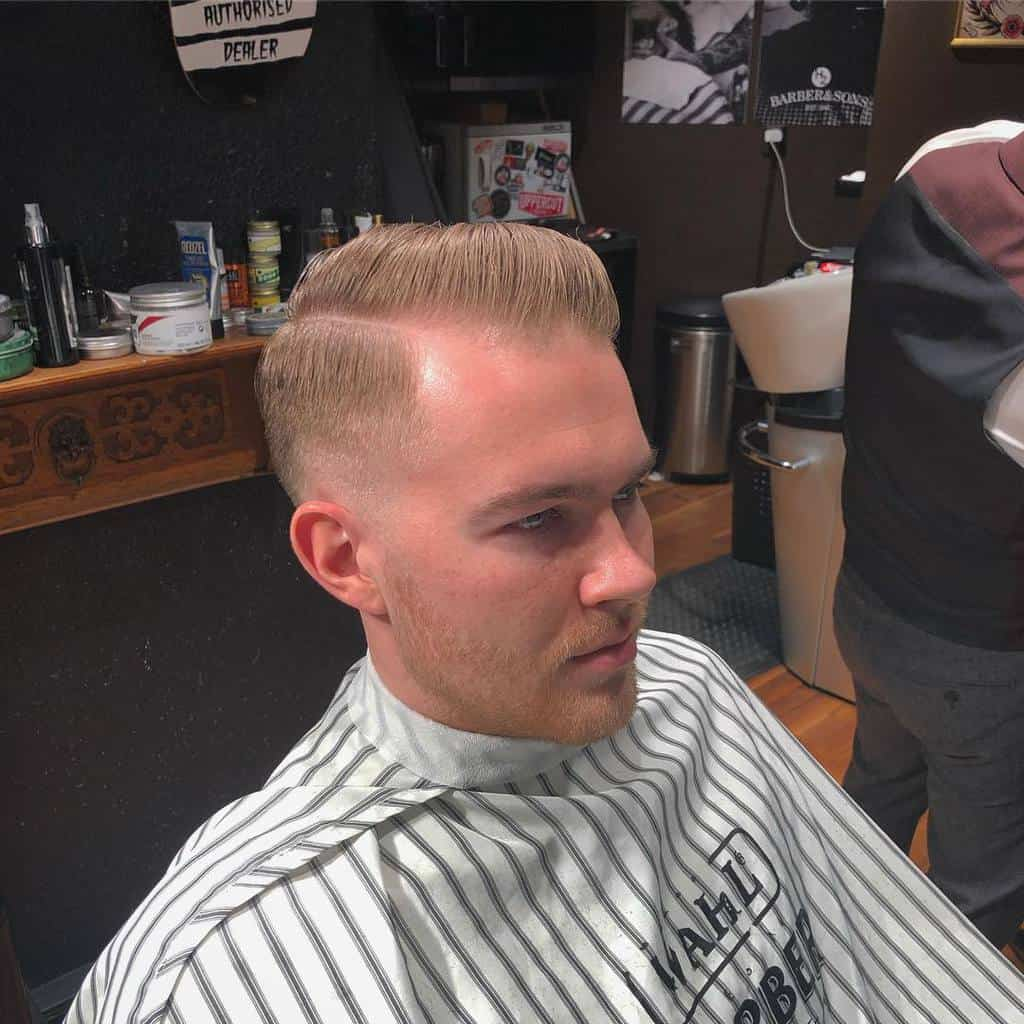 A peaky blinder haircut variation with a side-part on top paired with tapered sides