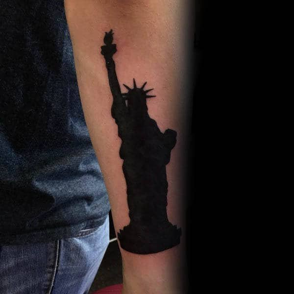 Silhouette Of Statue Of Liberty Tattoo On Mans Forearm