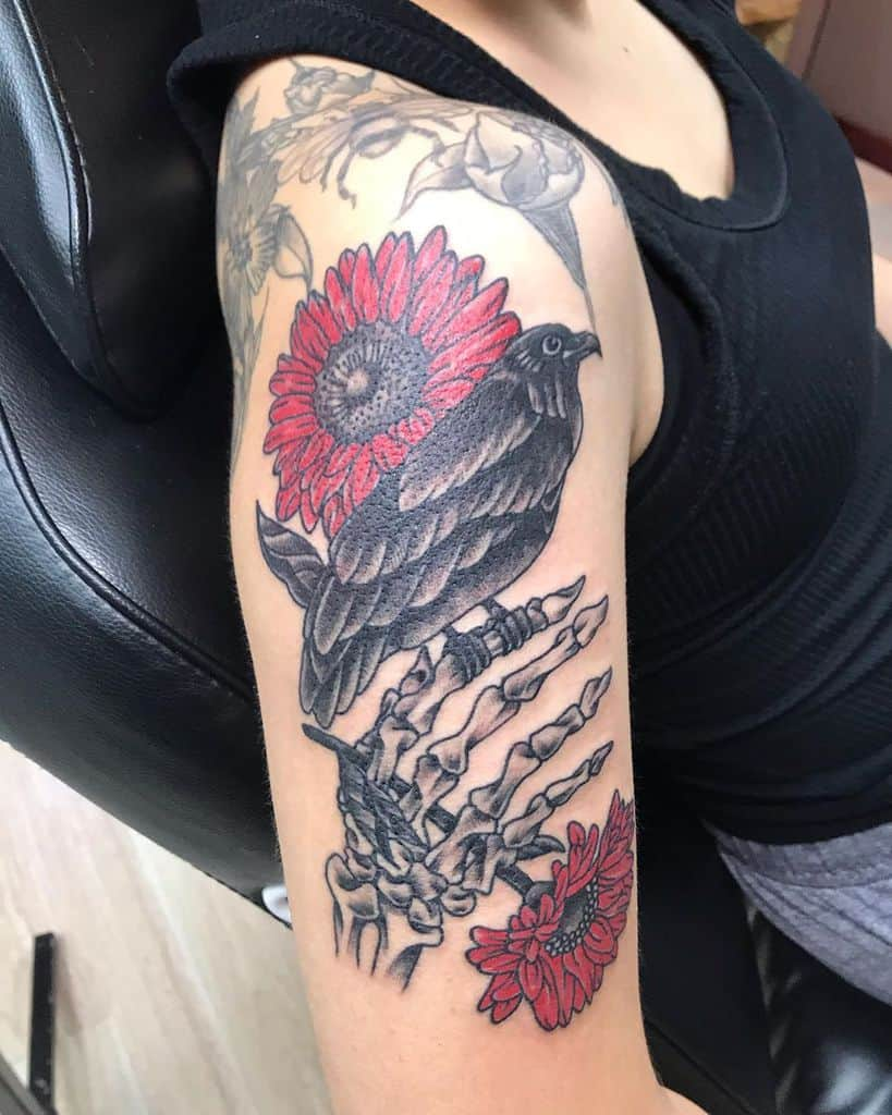Upper arm tattoo color crow with skeleton hand and red daisies