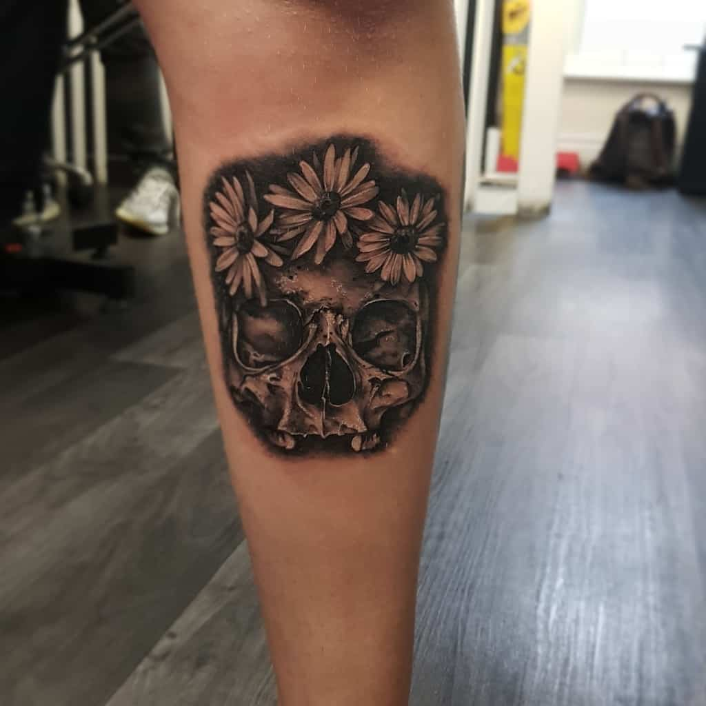 Calf tattoo realistic black and grey shading skull with a crown of daisies
