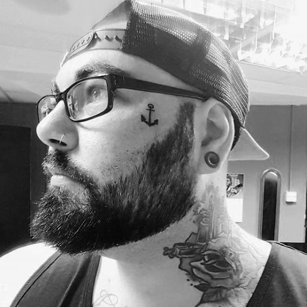 Small Face Tattoo Of Anchor On Male