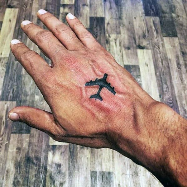 Small Guys Travel Tattoo Of Airplane On Hand With Black Ink