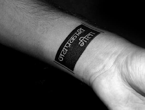 Small Manly Negative Space Blackwork Text Mens Wrist Tattoo