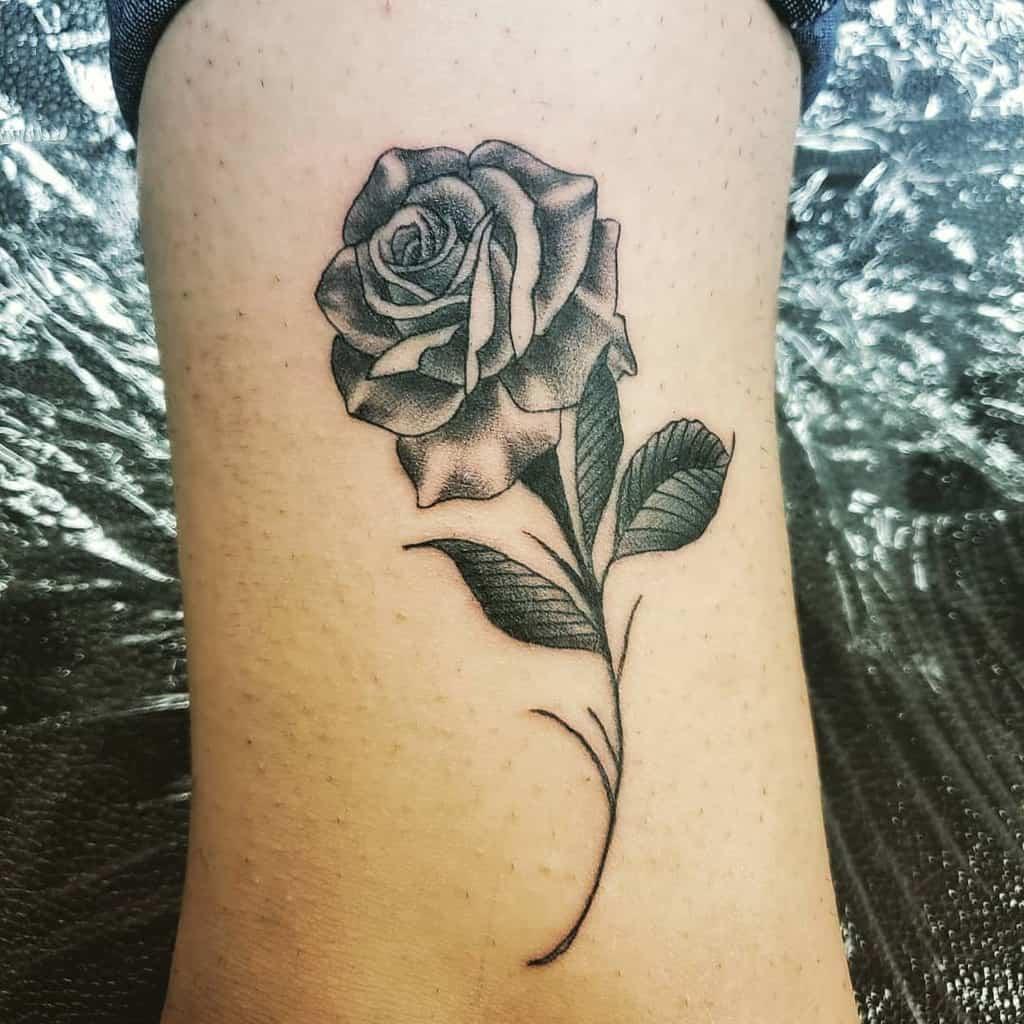 small minimalist rose with stem tattoos geotattts