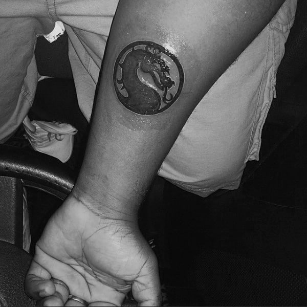 Small Simple Mens Mortal Kombat Logo Tattoo On Inner Forearm