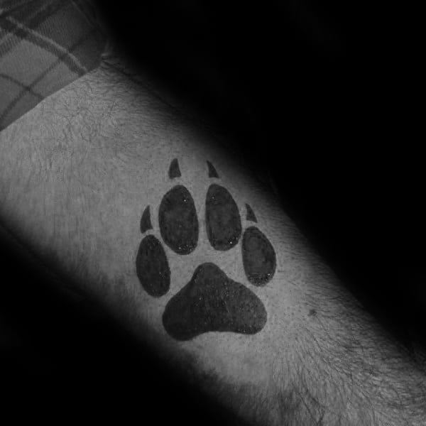 Small Simple Wolf Paw Forearm Solid Black Ink Tattoo On Guy