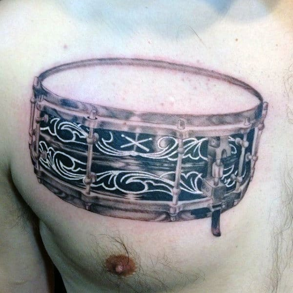 Snare Drum Tattoo On Mans Upper Chest With Decorative White Ink Design