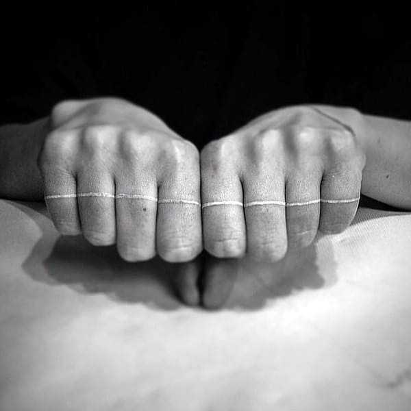 Solid White Ink Line Across Fingers On Mans Hand Tattoo