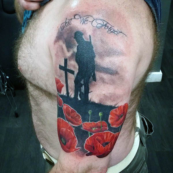 Solider Mourning Cross Grave With Poppy Flowers Tattoo On Upper Arm Of Man