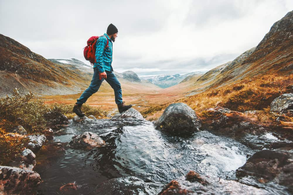 solo traveling backpacker hiking in scandinavian mountains