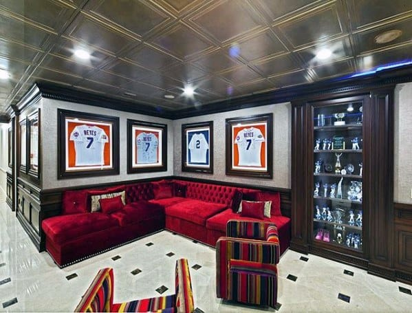 Sports Themed Basement Man Cave With Red Velvet Couch