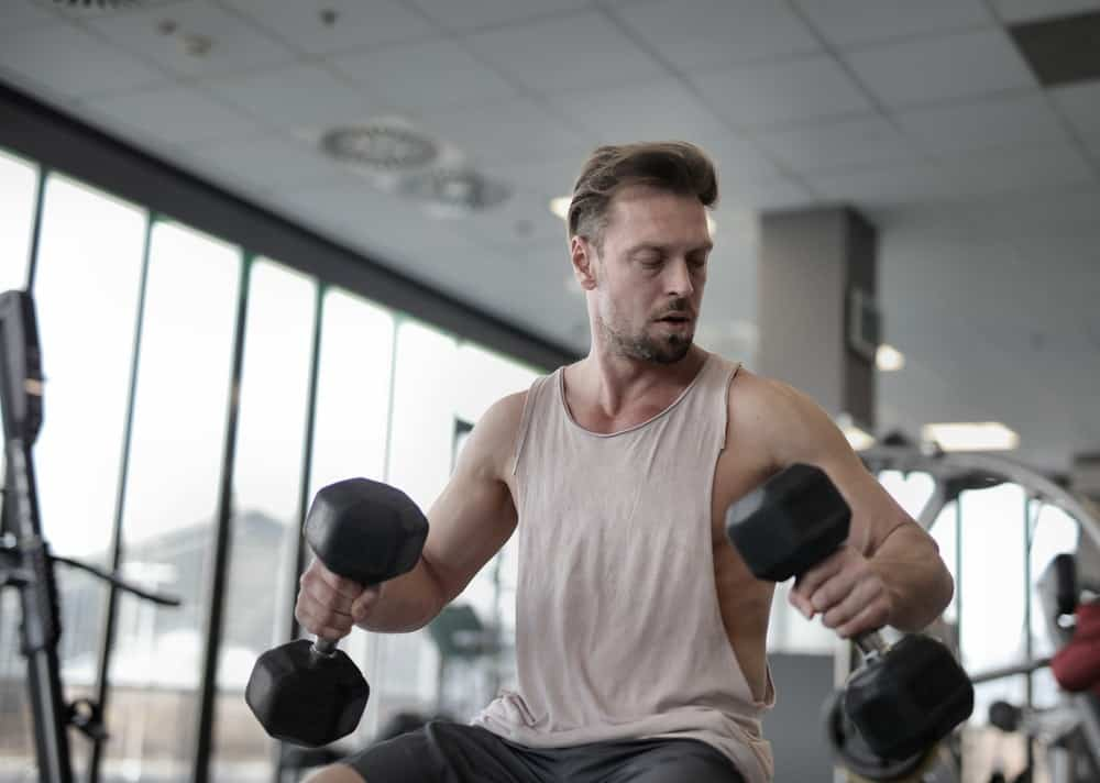 sportsman exercising with black dumbbells in gym