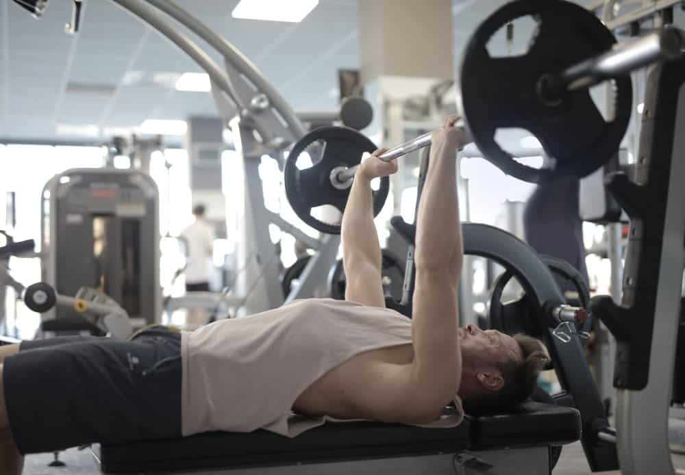 muscular sportsman training with heavy barbell in gym