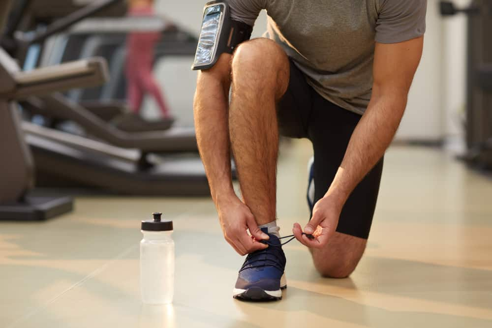 sportsman tying laces of blue shoes