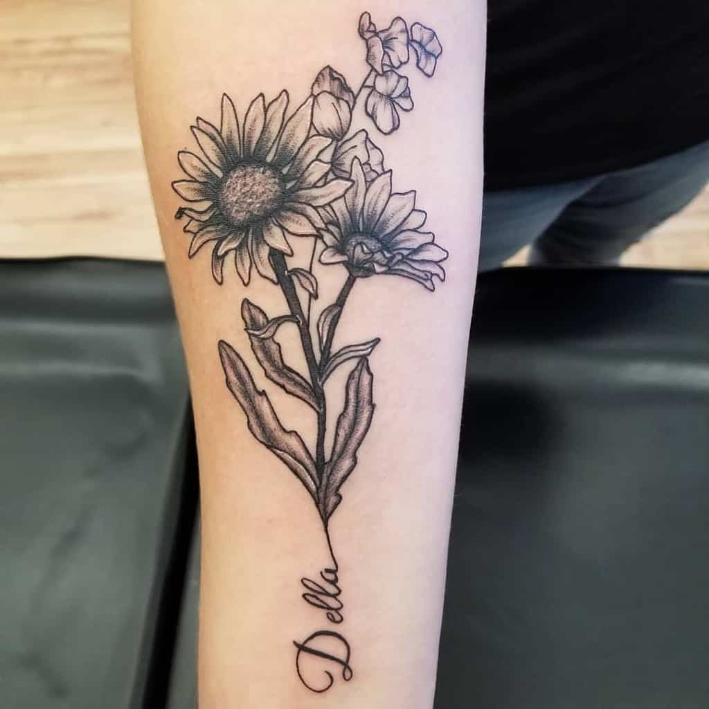 Forearm tattoo black and grey daisies with stem forming cursive script 'Della'