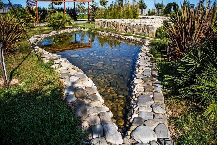 stone landscape backyard small shallow pond