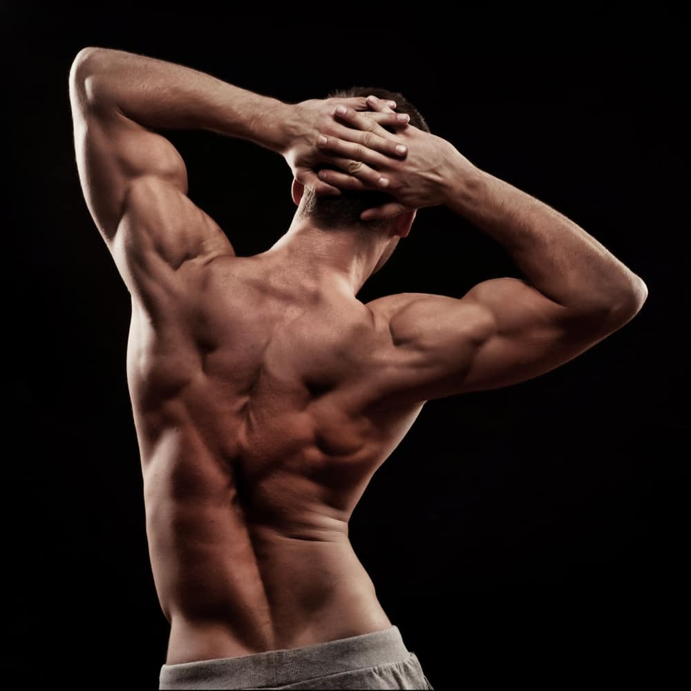 strong young athletic mans back isolated on black background