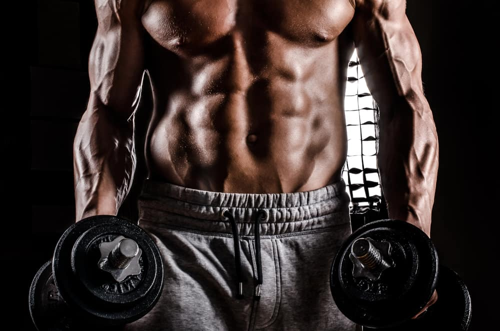 strong man male bodybuilder in action with dumbbells