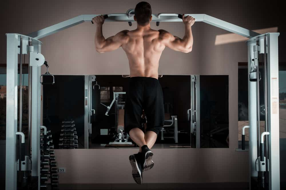 strong man doing pull ups inside gym