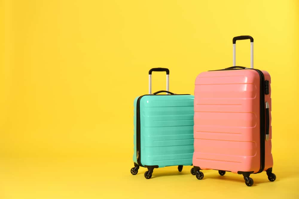 stylish suitcases isolated on yellow color background