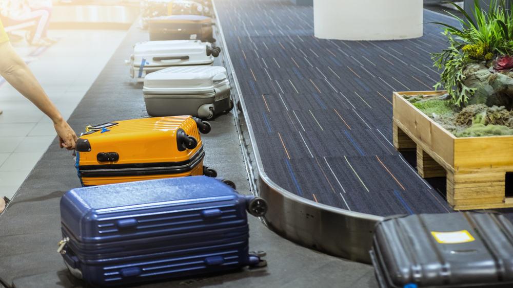 suit case on luggage conveyor belt at baggage claim