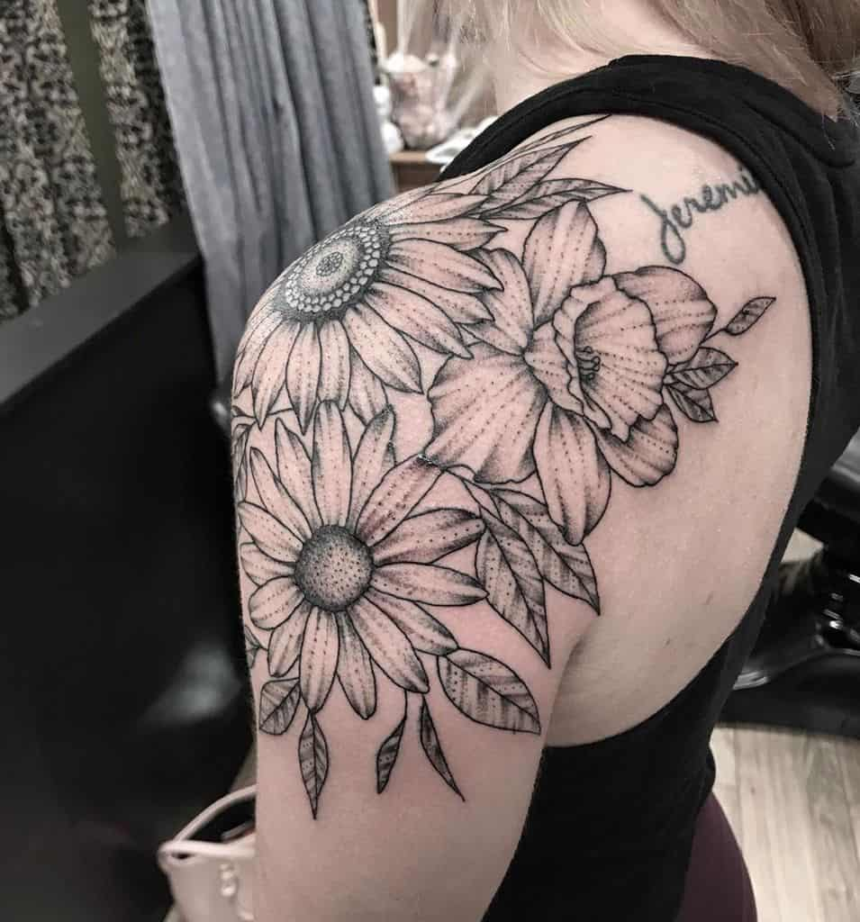 Shoulder wrapped tattoo large black and grey shading sunflower daisy and daffodil