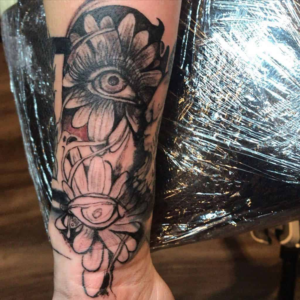 Forearm tattoo black and grey shading surreal daisies with eyes