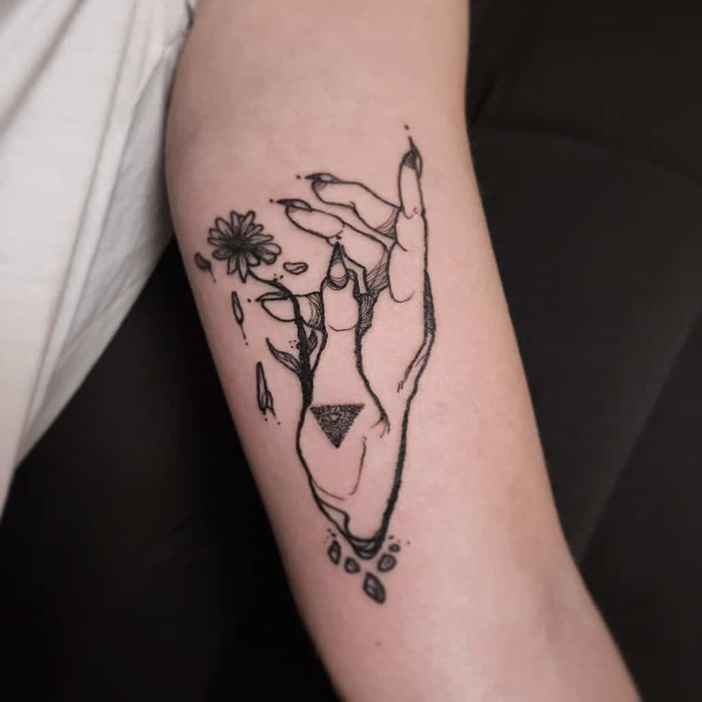 Bicep tattoo black and grey surreal witch hand daisy