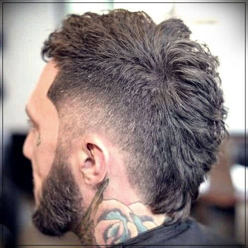 tattoo burst fade cut with faded hair along the hear connecting the beard