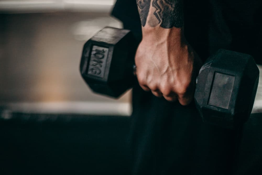 tattooed hand holds a 10kg dumbbell