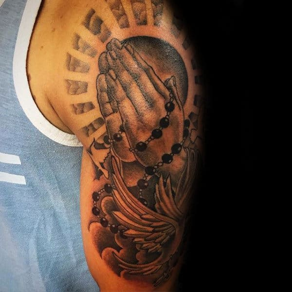 Tattoos Of A Rosary On Man With Sun Rays And Dove On Upper Arm